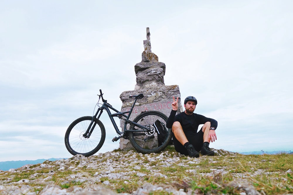 Slovenia mountain bike tour guide Marko resting at the top of an Alpine summit
