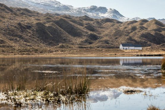 Still waters reflecting mountain hut and riders during our coast-to-coast Scotland mountain bike tour