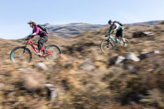 Riders descending rocky trail in Torridon mid-week on our coast-to-coast Scotland mountain bike tour