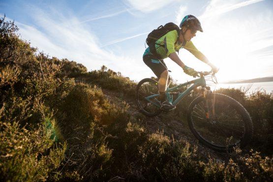 Mountain biker descending to Applecross on coast-to-coast Scotland mountain bike tour