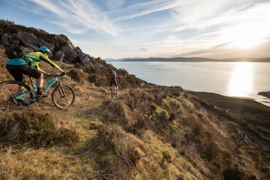 Mountain bikers descending in sunset, coast-to-coast Scotland mountain bike tour