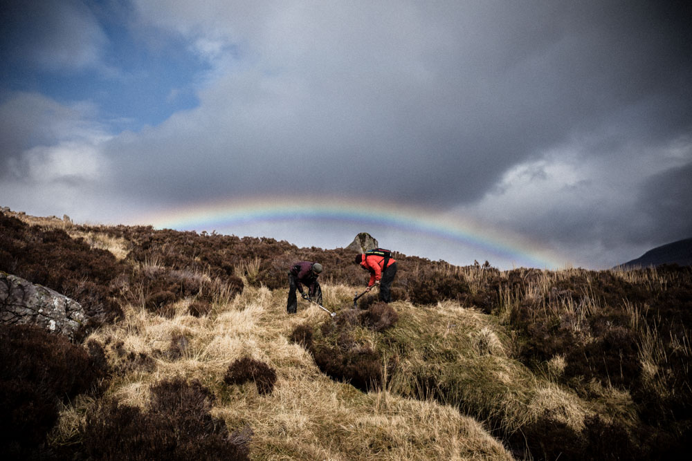 Maintaining trails under moody skies and a rainbow at the Take Care of Your Trails day at the Tea-Hut path in Torridon.