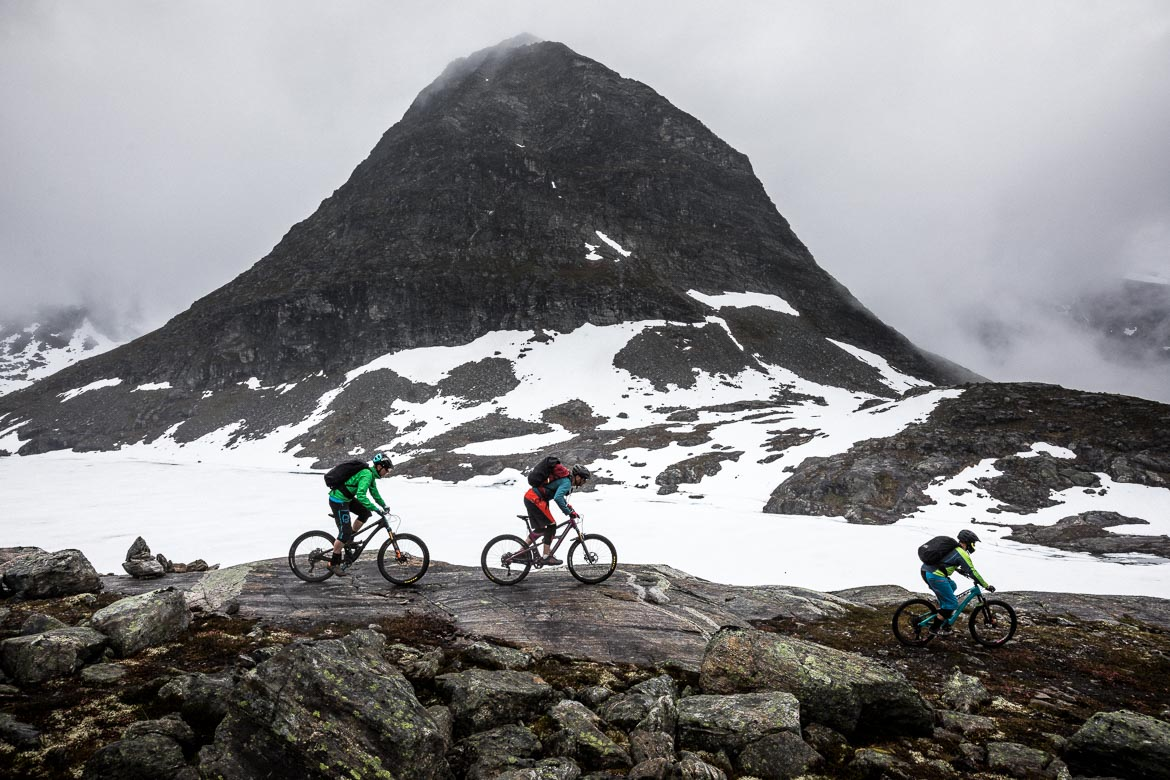 Mountain bikers dwarfed by a pyramidal peak during our mountain bike tour Norway. One of our mountain biking adventures in Europe.