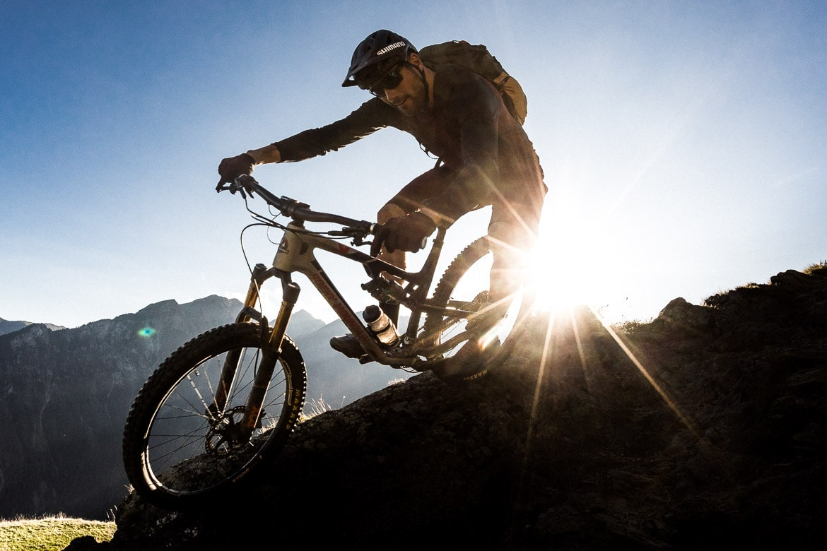 Thomas Vanderham descending towards San Romero at sunset during our mountain bike tour Switzerland.