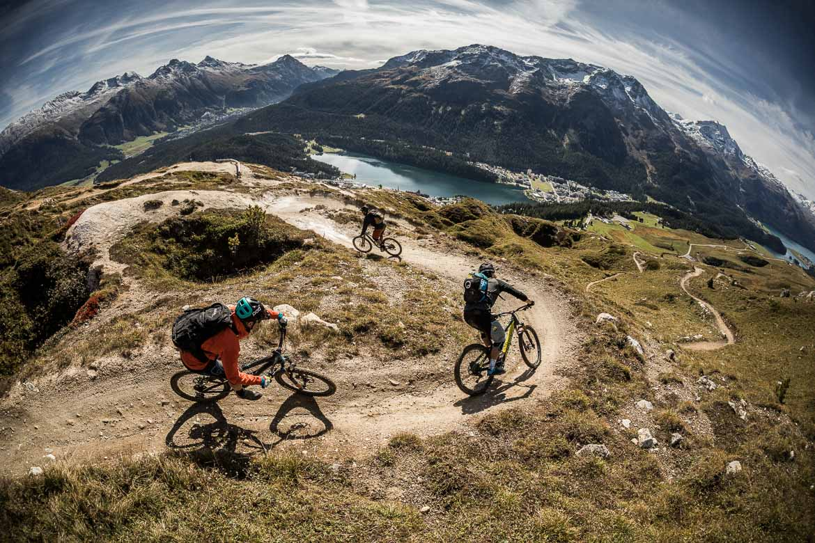 Mountain bikers high above St Moritz on one of the region's many flow trails, part of our mountain bike tour Switzerland.