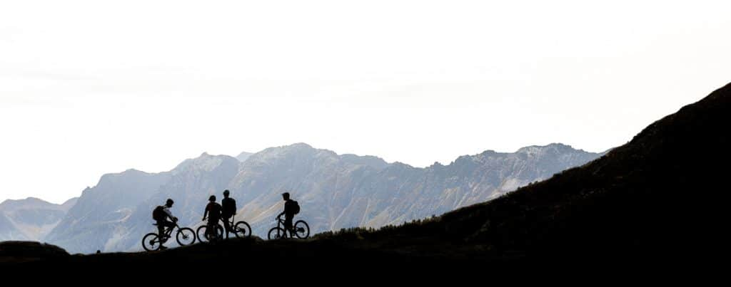 Mountain bikers stopping to catch their breath in the mountains above Poschiavo during our Switzerland mountain biking tour