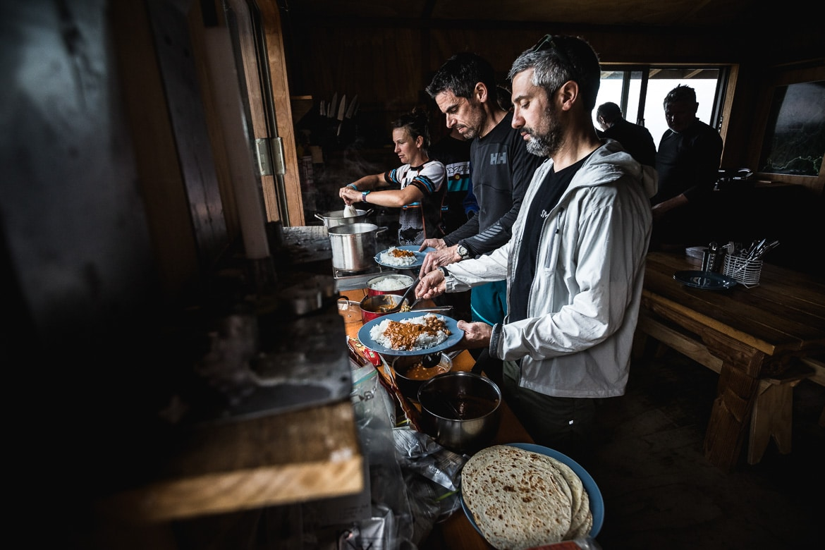 Mountain bikers eating dinner in the Ghost Lake Hut after riding the Old Ghost Road during the International Yeti Tribe New Zealand mountain bike tour.