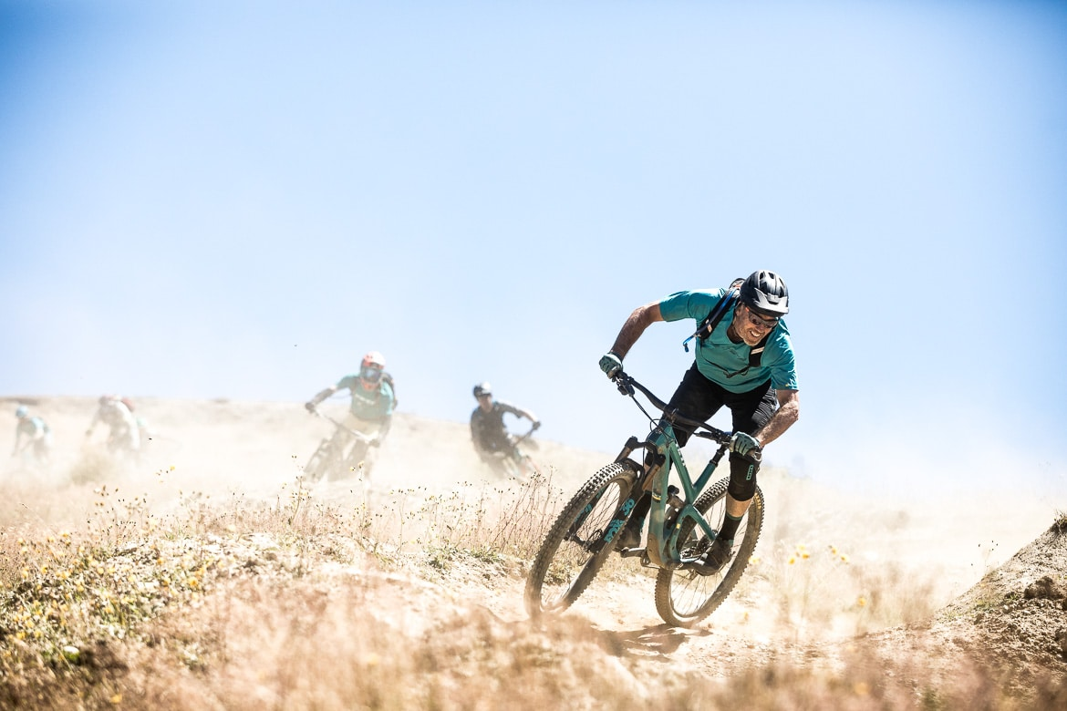 Riding the rollercoaster of trails at Cardrona Bike Park near Queenstown during the International Yeti Tribe New Zealand mountain bike tour. Featured in our mountain biking tips.