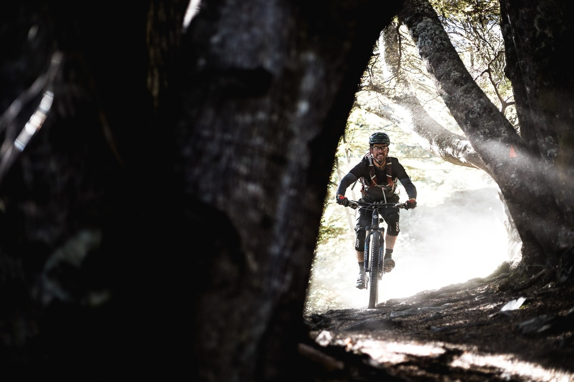 Mountain biker riding the roots trails in Queenstown during the International Yeti Tribe New Zealand mountain bike tour.