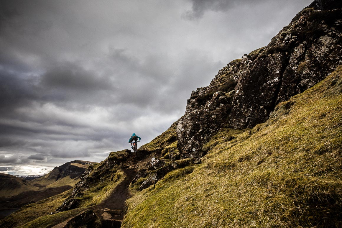 Mountain biker riding the Quiraing on the Isle of Skye under moody skies.