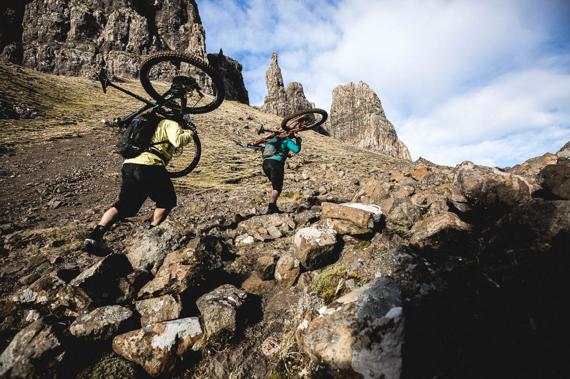 Mountain bikers hike a biking on the Isle of Skye whilst riding the Quiraing.