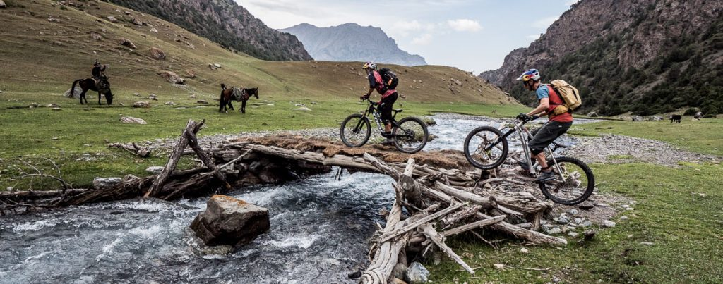 Rene Wildhaber and Tom Oehler crossing a bridge whilst mountain biking in Kyrgyzstan.
