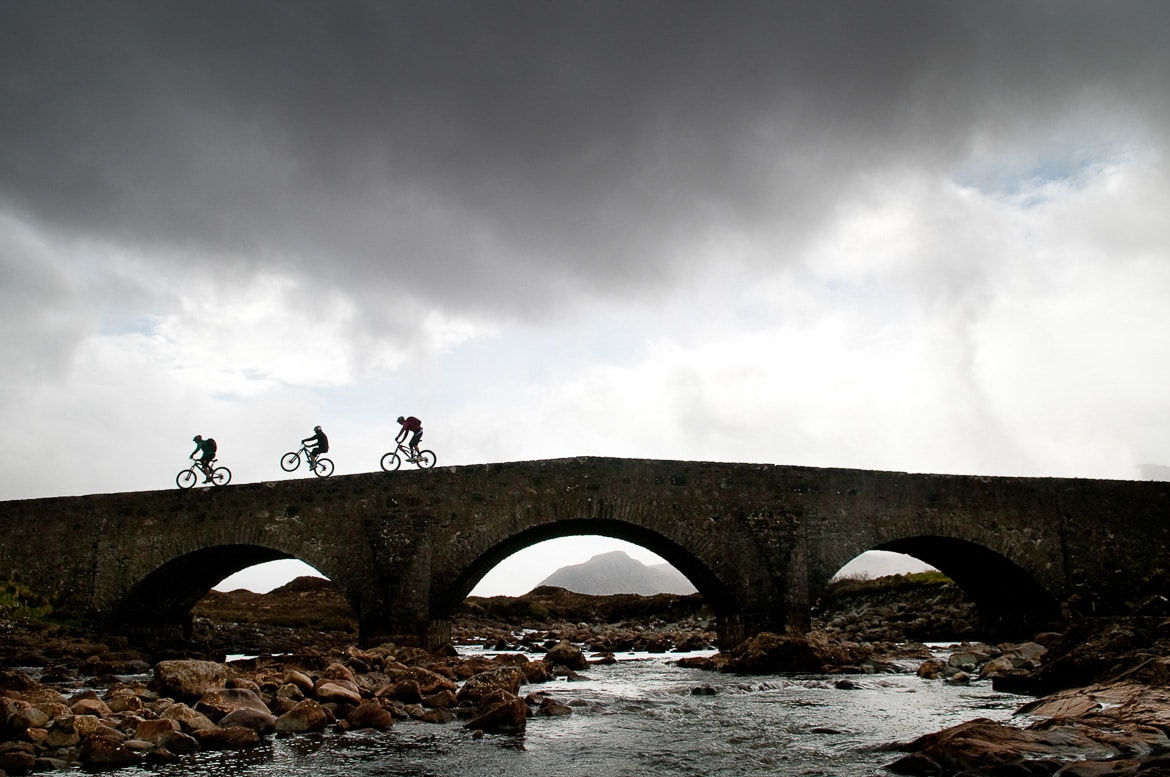 Riding over a bridge on the Isle of Skye Heli-Biking with Danny MacAskill, Steve Peat, Hans Rey in the Torridon mountains and Isle of Skye