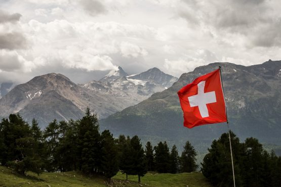 The Swiss flag fluttering over the mountains on a E-MTB Tour In Switzerland