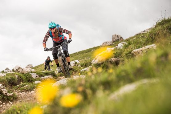 Blasting through the lush yellow flowers on a E-MTB Tour In Switzerland