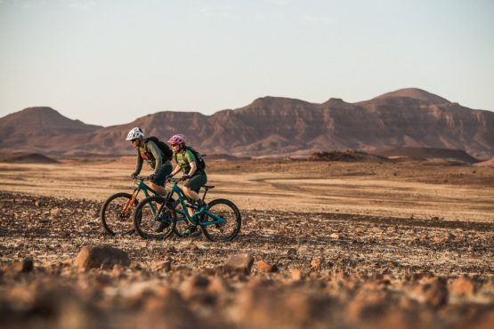 Crossing a flat plain surrounded by mountains on a mountain bike safari tour Namibia