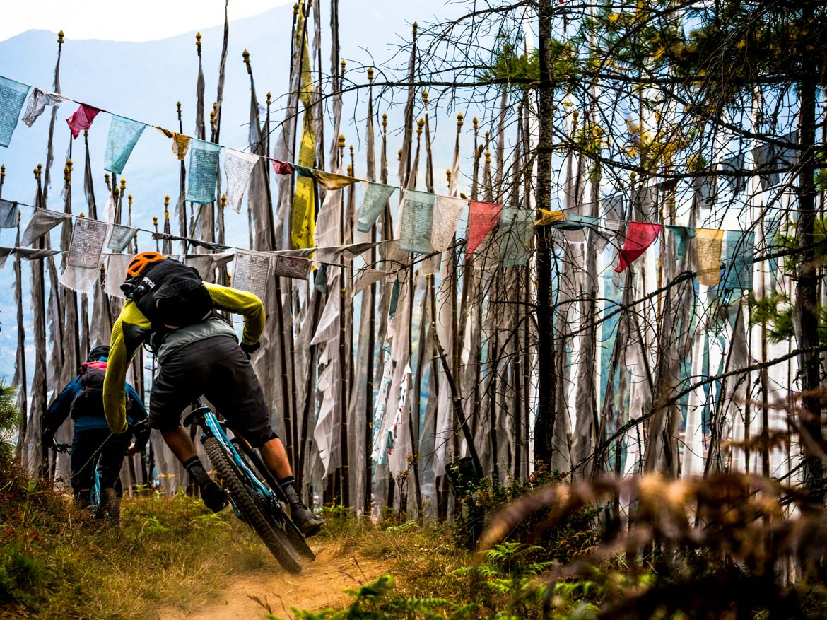 Racing through the flags whilst mountain biking in Bhutan