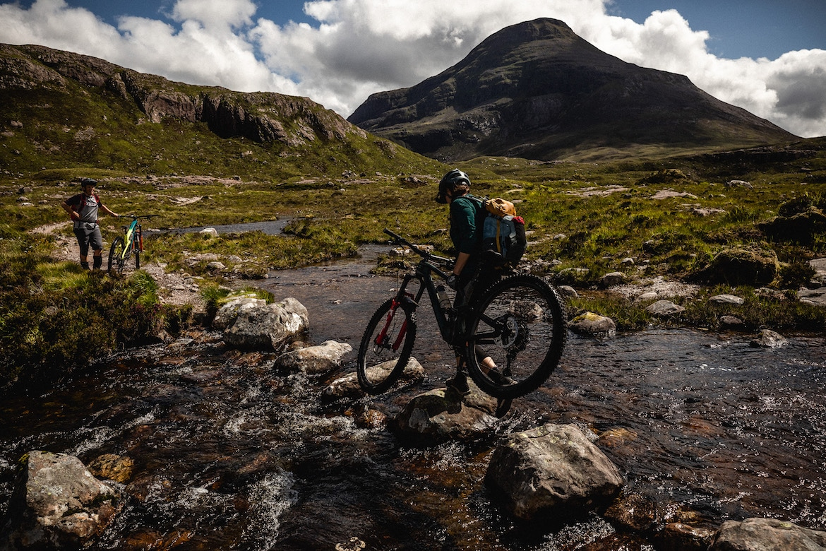 Tracy Moseley + Manon Carpenter crossing a Highland river