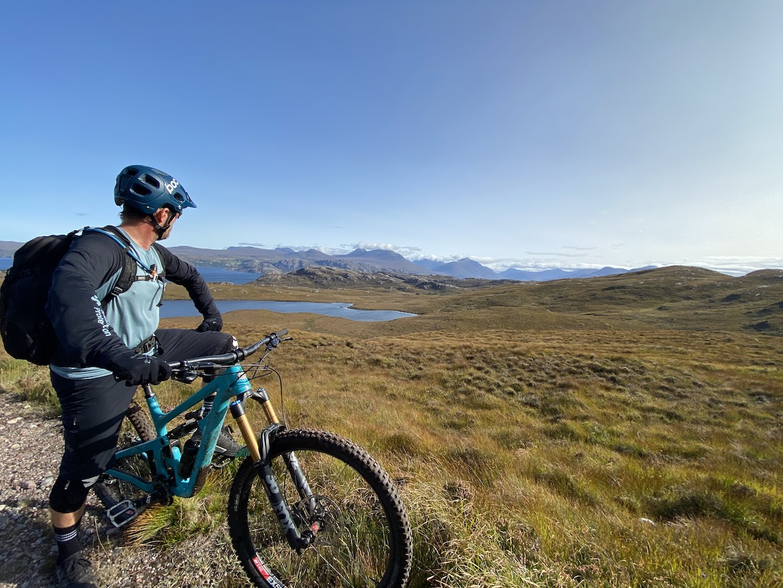 Highland MTB adventure, mountain biker overlooking Skye